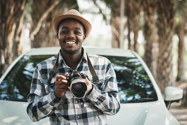 Homem africano feliz viajante na estrada com um carro branco e segurando uma câmera