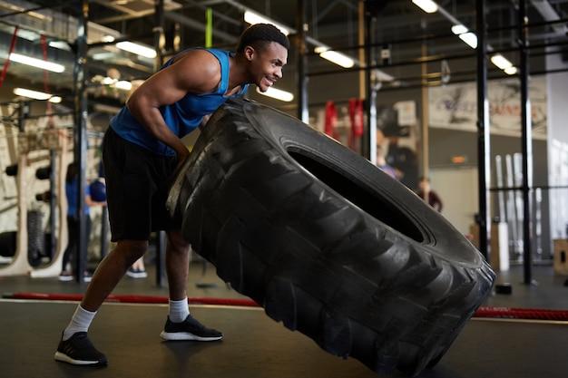 Homem africano forte lançando pneus no ginásio