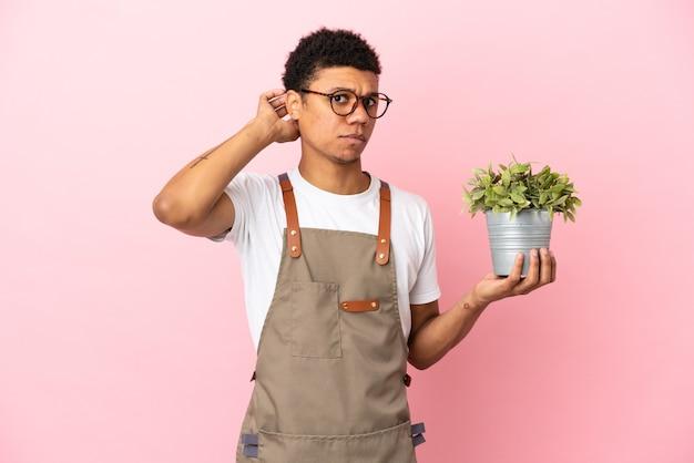 Homem africano jardineiro segurando uma planta isolada em um fundo rosa, tendo dúvidas