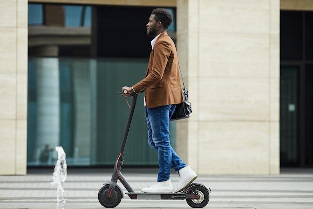 Homem africano montando fundo scooter elétrico