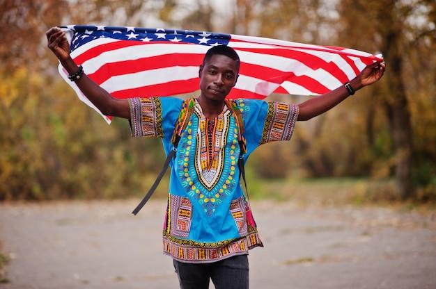 Homem africano na camisa tradicional de áfrica no outono park com bandeira eua.