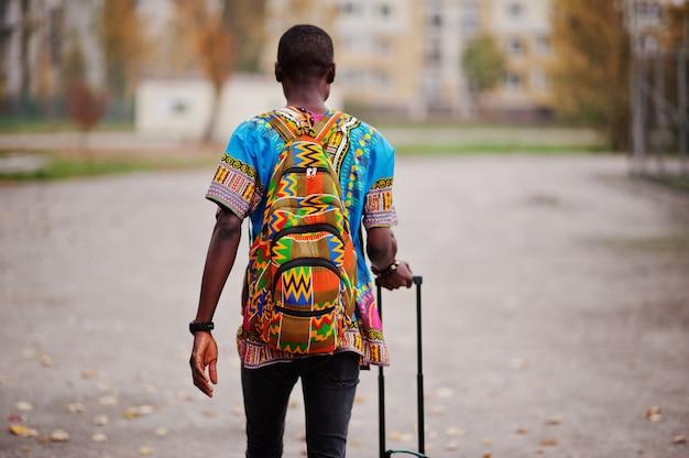 Homem africano na camisa tradicional de áfrica no outono park com mochila e mala. viajante emigrante.