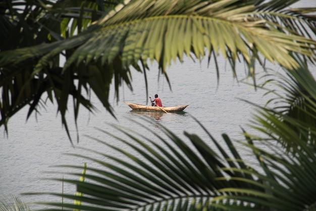 Homem africano na velha canoa pescando no lago kivu, ruanda