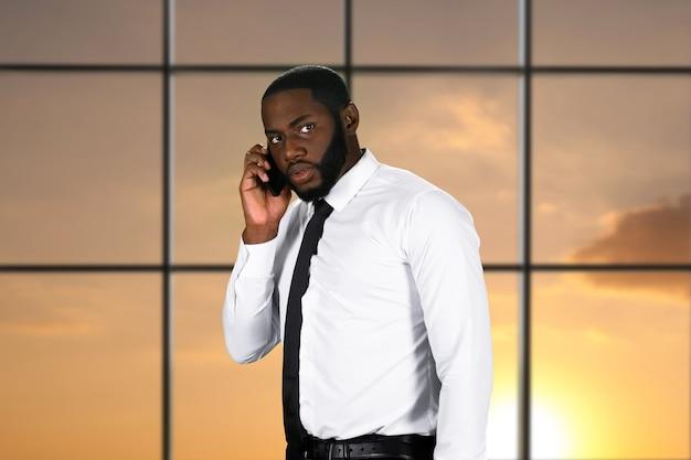 Homem africano nervoso com o celular.