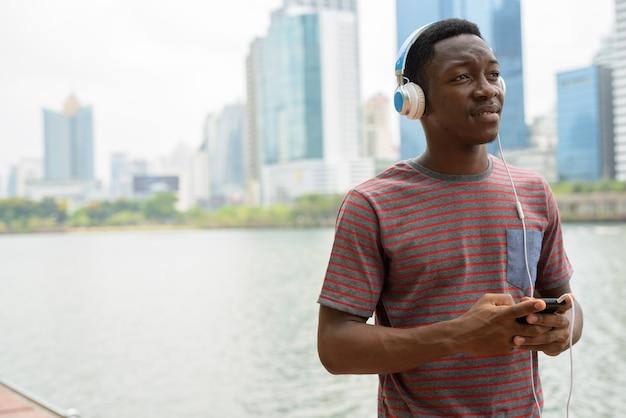 Homem africano no parque usando telefone celular e ouvindo música com fones de ouvido enquanto pensa