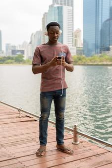 Homem africano no parque usando telefone celular e ouvindo música com fones de ouvido