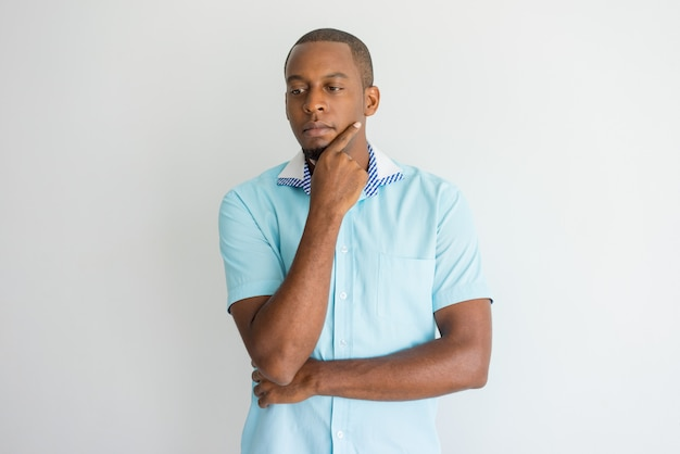 Homem africano novo considerável introspectivo que esfrega o queixo e que olha para baixo.