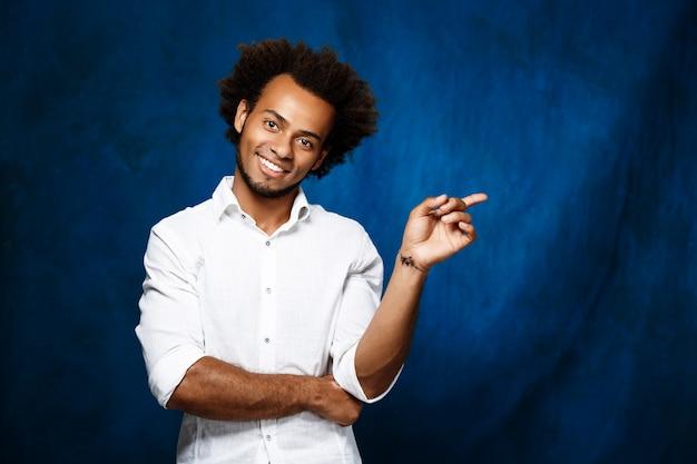 Homem africano novo que aponta o dedo no lado sobre a parede azul.