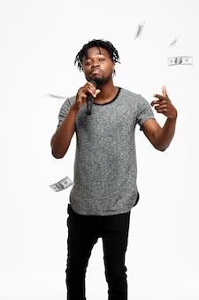 Homem africano novo que canta no microfone no branco.