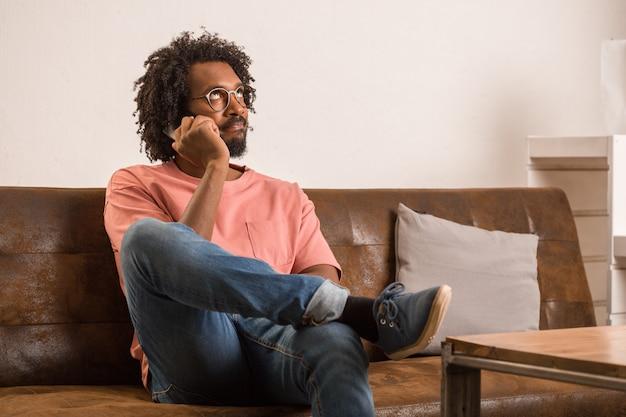Homem africano novo que fala no móbil, é sério e pensativo.
