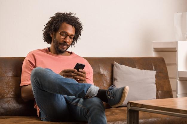 Homem africano novo que fala no móbil, sentando-se em um sofá, está sorrindo e positivo.