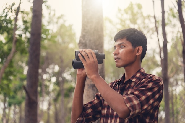 Homem africano novo que olha com binocular na floresta, conceito do curso.