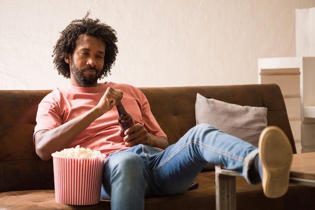 Homem africano novo que olha um filme que guarda uma cubeta da pipoca e que bebe uma cerveja.