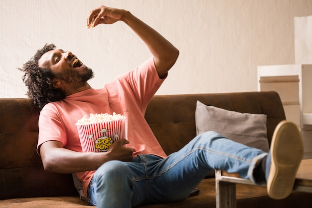 Homem africano novo que presta atenção a um filme que prende uma cubeta da pipoca.