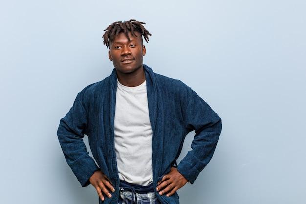 Homem africano novo que veste o pijama seguro mantendo as mãos nele quadris.