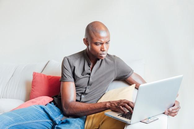 Homem africano novo raspado que senta-se no sofá usando o portátil