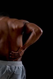 Homem africano novo saudável que exercita a dor para trás.