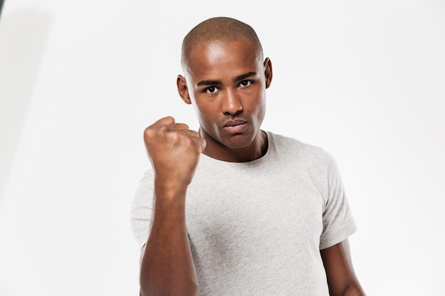 Homem africano novo sério que mostra o punho.