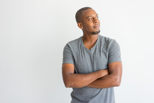 Homem africano novo sonhador pensativo com os braços cruzados que olham afastado.