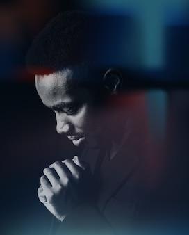 Homem africano orando por deus em um quarto escuro com vazamentos de luz