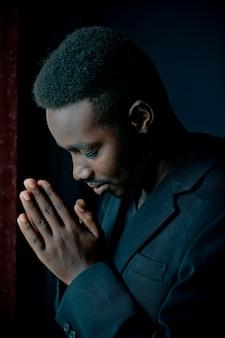 Homem africano orando por deus no quarto escuro.