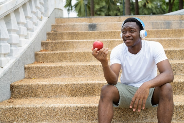 Homem africano ouvindo música com fones de ouvido e segurando uma maçã vermelha