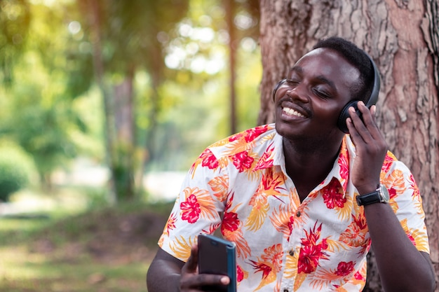 Homem africano, ouvir música de smartphone com fones de ouvido