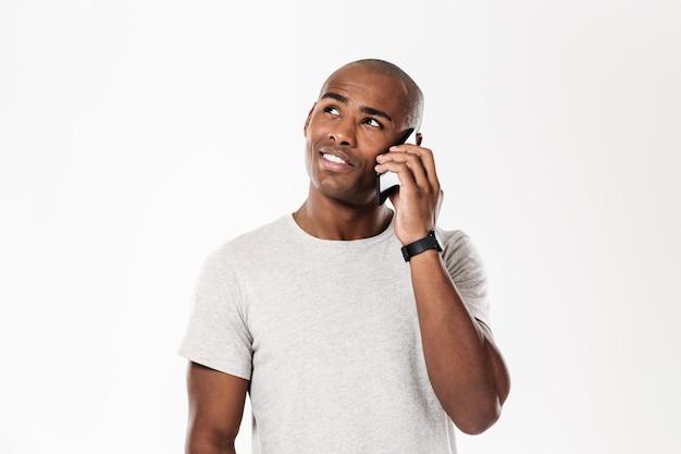 Homem africano pensativo, falando pelo smartphone e olhando para cima