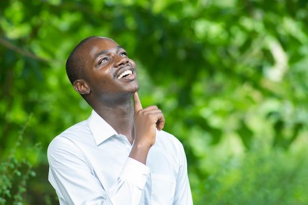 Homem africano que pensa na natureza verde.