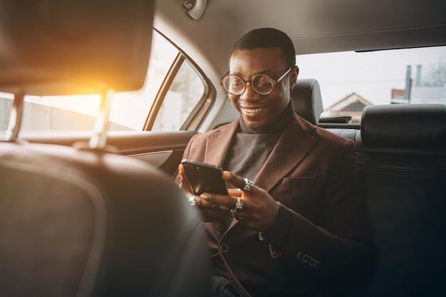 Homem africano que usa o smartphone ao sentar-se no assento traseiro no carro.