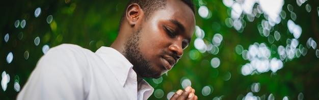 Homem africano rezando para agradecer a deus com reflexo de luz e bokeh bonito em preto e branco