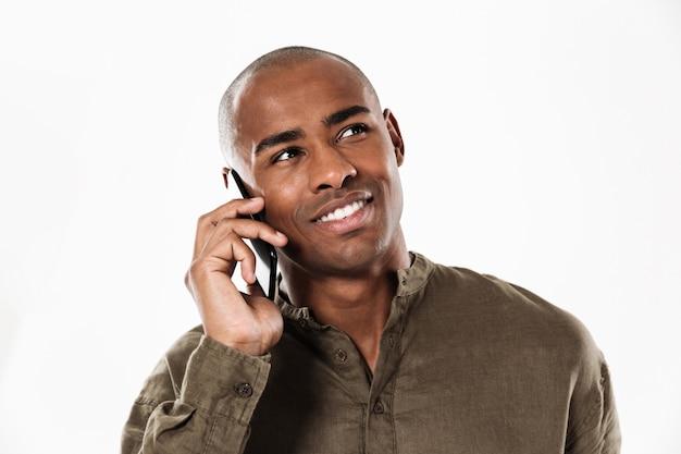 Homem africano satisfeito falando pelo smartphone e olhando para longe