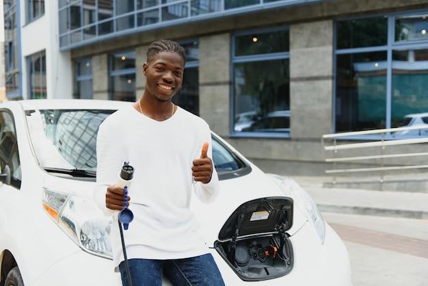 Homem africano segurando o cabo de carga disponível, em pé perto de um carro elétrico de luxo.