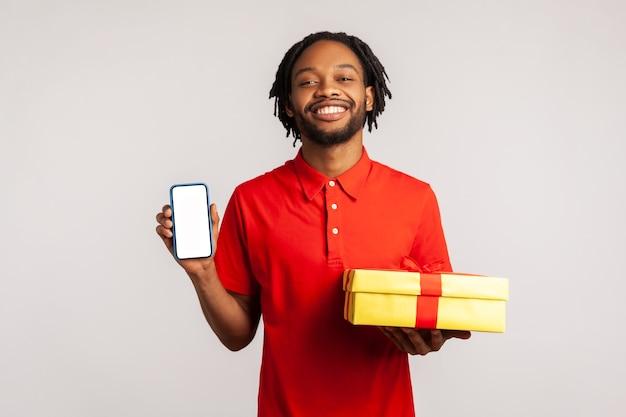 Homem africano segurando uma caixa de presente e um telefone celular com tela em branco para publicidade de compras online.
