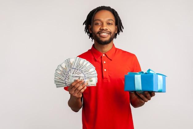 Homem africano segurando uma caixa de presente, notas de dólares, sorrindo para a câmera, reembolso e empréstimo bancário.