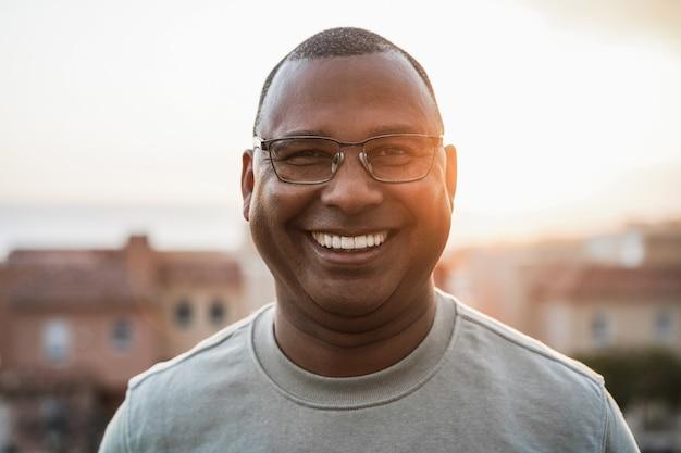 Homem africano sênior feliz olhando para a câmera ao ar livre ao pôr do sol - foco no rosto