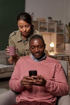Homem africano sentado na poltrona usando seu telefone celular com uma mulher em pé atrás dele e bebendo café
