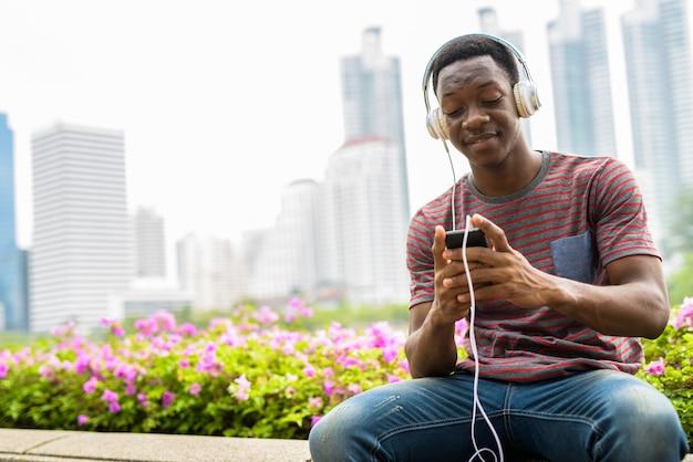 Homem africano sentado no parque, ouvindo música com fones de ouvido e usando o telefone celular