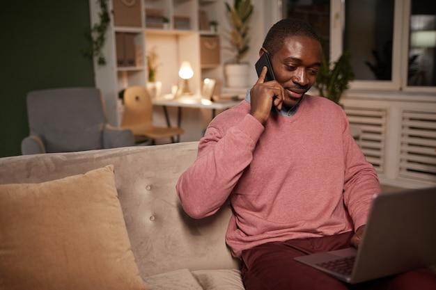 Homem africano sentado no sofá com o laptop ajoelhado falando no celular e trabalhando online
