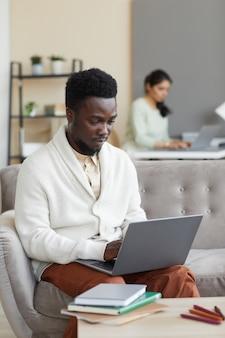 Homem africano sentado no sofá em frente à mesa com livros e digitando no laptop que ele está aprendendo online em casa