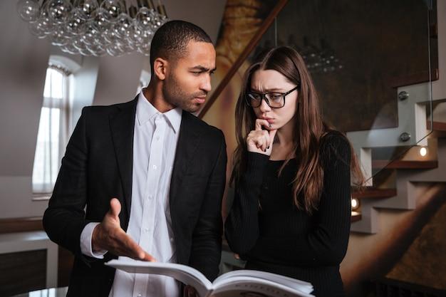 Homem africano sério de terno falando com uma mulher de óculos e apontando para o diário