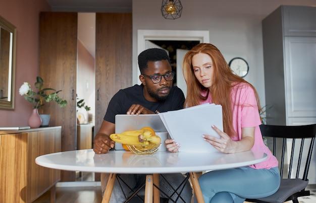 Homem africano sério lendo jornais e mulher caucasiana discutem contas internas não pagas