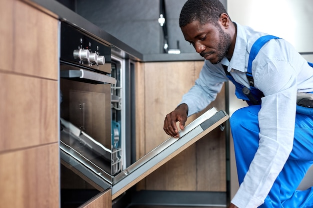 Homem africano sério ou trabalhador de serviço em roupas especiais instala, desmonta ou realiza manutenção da máquina de lavar louça embutida nos móveis da cozinha, vista lateral em cara negro de macacão azul