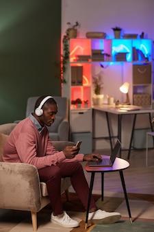 Homem africano sério usando fones de ouvido sem fio, trabalhando online no celular e no laptop no escritório