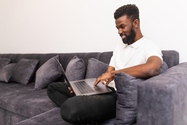 Homem africano sorridente e feliz assistindo e trabalhando em um computador laptop em casa