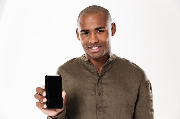 Homem africano sorridente, mostrando a tela do smartphone em branco e olhando