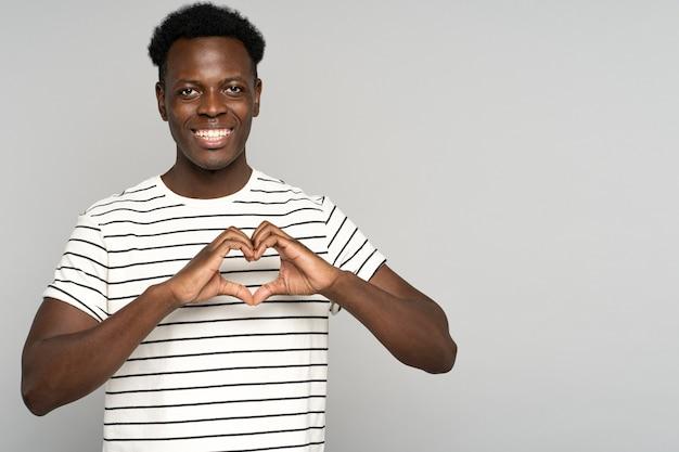 Homem africano sorridente, mostrando o sinal do coração com os dedos, sente-se grato pelo amor, grato e apoio.