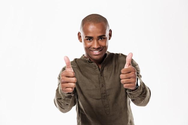 Homem africano sorridente, mostrando os polegares e olhando