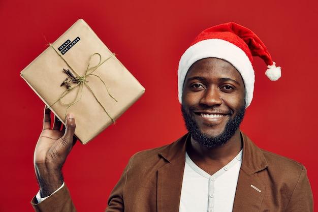 Homem africano sorridente, usando chapéu de papai noel no vermelho