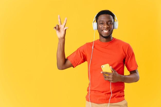 Homem africano sorridente usando fones de ouvido divertido fundo amarelo